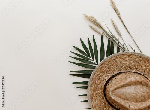 Mieszkanie leżał ze słomy kapelusz i liść tropikalny liść palmowy na pastelowe tło. Minimalistyczna stylizowana kompozycja
