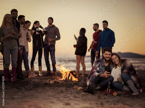 Foto Murales Couple enjoying bonfire with friends on beach