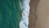 Top down aerial footage of the waves rolling in onto the beach sand. - 212985944