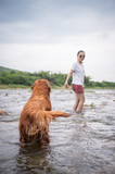 Golden Retriever and master play in the water. - 212987569