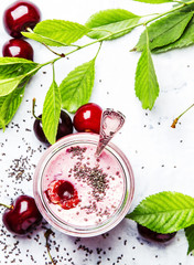 Pink cherry smoothies with yoghurt and chia seeds, gray background, top view