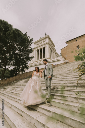 Obraz na płótnie Bride and groom walking outdoors at Spagna Square and Trinita' dei Monti in Rome, Italy