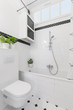 Plants above toilet in white and black bathroom interior with cabinet above bathtub. Real photo