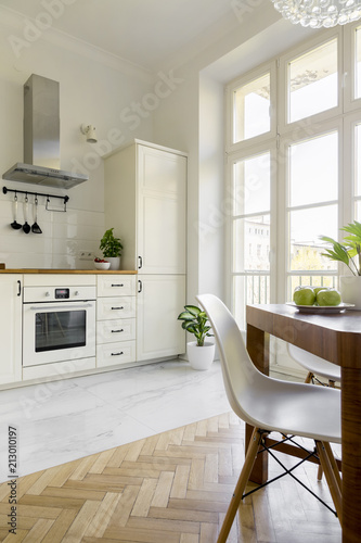 White chair at wooden dining table in simple kitchen interior with window. Real photo