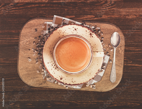 cup of coffee with roasted beans on wooden table
