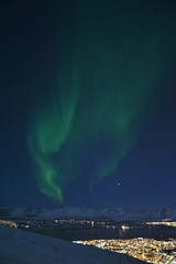 The northern lights (Aurora Borealis) and the city scape from Fjellheisen Peak over the city © BAHADIRARAL