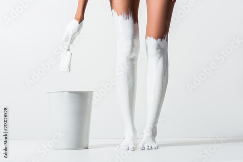 cropped image of woman with legs painted with white paint holding brush above bucket on white - 213026528