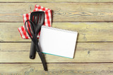 Blank sheet of opened notepad and kitchen utensils on  table with tablecloth, copy space - 213030734