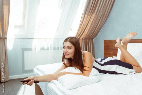 Leinwanddruck Bild woman relaxing in hotel room and looking tv