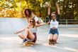 Three excited young girls with skateboards