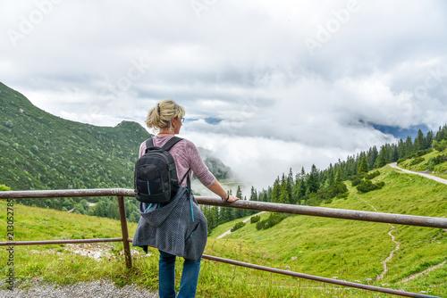 Poster Frau mit Rucksack Wander in den Bergen Blick auf die Landschaft im Sommer