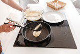 Cropped photo of woman cooking in kitchen at home, and frying pancakes on modern stove - 213065181