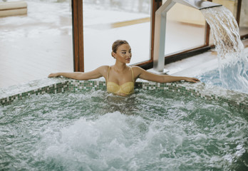 Pretty young woman relaxing in the bubble bath pool
