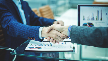 handshake financial partners on the background of the workplace with financial papers © yurolaitsalbert