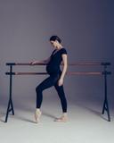 Young beautiful pregnant ballerina is posing in studio - 213071383