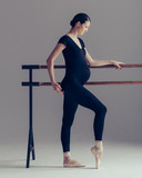 Young beautiful pregnant ballerina is posing in studio - 213071551