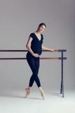 Young beautiful pregnant ballerina is posing in studio - 213071773