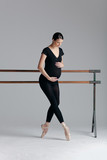 Young beautiful pregnant ballerina is posing in studio - 213071789