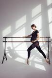Young beautiful pregnant ballerina is posing in studio - 213071986