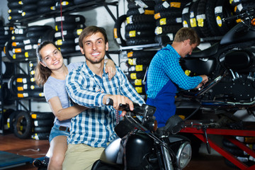 couple sitting on new motorbike in workshop.
