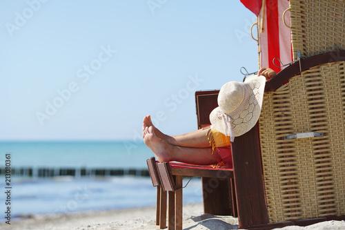 Leinwandbild Motiv Frau erholt sich im Strandkorb