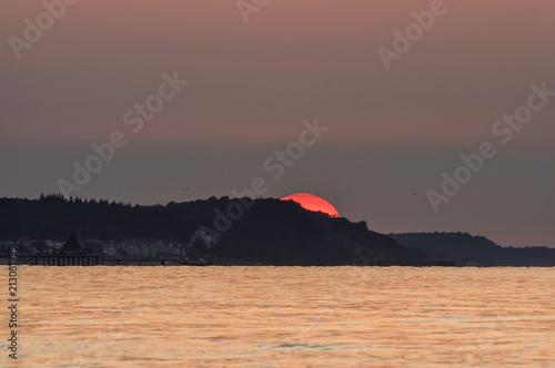 Foto Murales Słońce zachodzące nad morskim półwyspem.