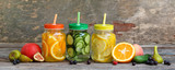 Different drinks, fruits and vegetables on wooden background.