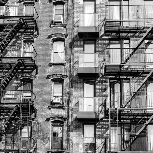 Foto Murales A fire escape of an apartment building in New York city. Graphical black and white image.