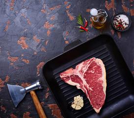Raw T-bone steak on iron grill pan