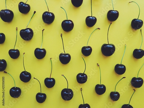 Sweet cherries on a yellow background. Cherry pattern. - 213106100