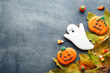 Halloween gingerbread cookies with candies and dry leafs on grey wooden table - 213110534