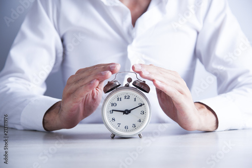 Poster man holding clock on table