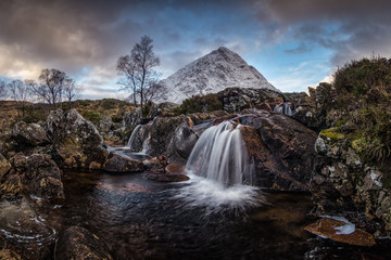 Amazing natural landscape of Scotland. A waterfall with snow covered mountain in the background. Scotland is just so beautiful.
