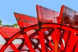 Red Riverboat Paddle Wheel in a River with Trees - 213125750