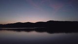 Drone flying over lake in austria during sunset with mountain range in background. - 213165362