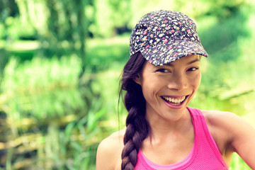 Young happy healthy Asian girl smiling to the camera. Chinese Caucasian multiracial woman wearing fashion cap and hair braid in summer park green grass background. Natural beauty.