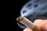 Gefährlicher Qualm aus einer Zigarette vor schwarzem Hintergrund - 213179377