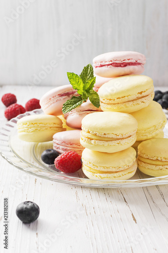 Fotobehang Macarons Different types of macarons on white wooden table. Copyspace.