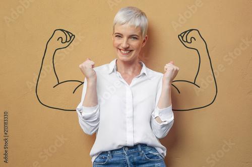 Leinwandbild Motiv Blond Frau an der Wand / Muskeln / Kraft / Power