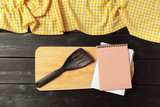 Blank sheet of opened notepad and kitchen utensils on  table with tablecloth, copy space - 213205106