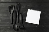 Blank sheet of opened notepad and kitchen utensils on  table with tablecloth, copy space - 213205154