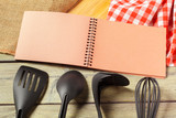 Blank sheet of opened notepad and kitchen utensils on  table with tablecloth, copy space - 213205305