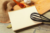 Blank sheet of opened notepad and kitchen utensils on  table with tablecloth, copy space - 213205321