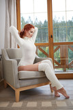 Beautiful autumn red hair model with waving glow hair.Sun light on sunset. Portrait of romantic female in sweater.