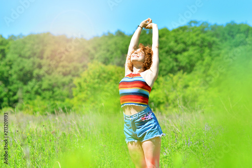 Fotobehang Lime groen Summer background with a happy girl. Girl pulls her hands to the sky.