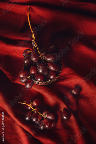 Foto Murales close-up shot of grapes in vintage metal bowl on red drapery