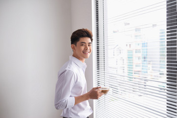 Portrait of a confident young businessman holding a cup of coffee while standing near office window, intelligent men in white shirt while resting after meeting