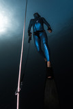 Freediver ascends from a depth along the rope holding a safety leash in a hand. - 213217155