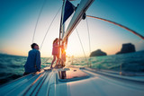 Couple works with ropes on the sail boat at sunset. Tilt shift effect applied - 213218524