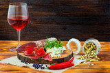 Sliced cured bresaola with spices and a glass of red wine. - 213218577